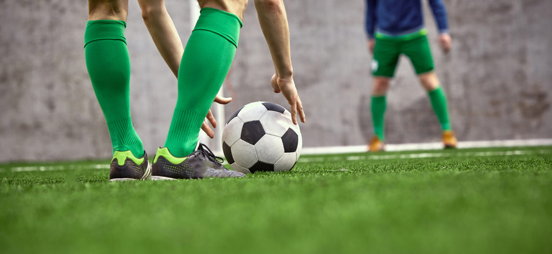 Fussballspieler setzt sich den Ball
